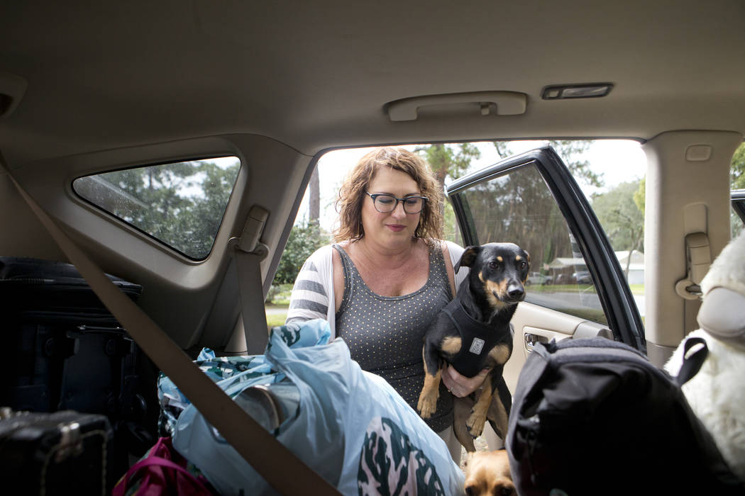 Julie Logsdon loads her dogs Tobias and Luna into her car in Panama City, Fla., as Hurricane Michael approaches on Tuesday, Oct. 9, 2018. She is evacuating with her husband, four pets and belongin ...