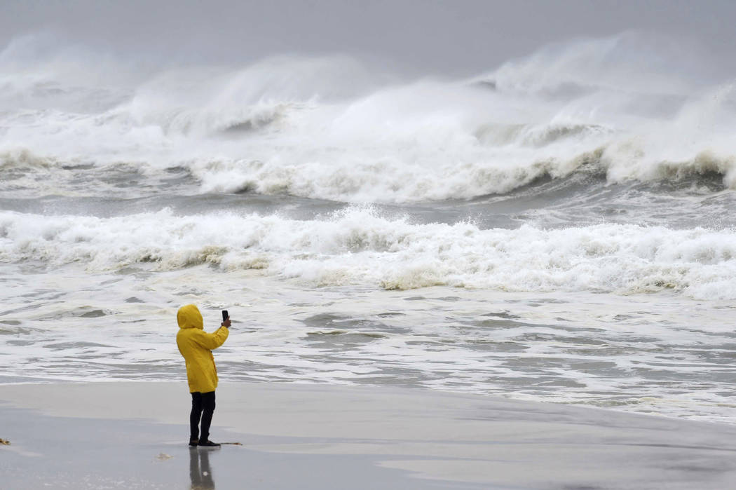 An unidentified person takes pictures of the surf and fishing pier on Okaloosa Island in Fort Walton Beach, Fla., on Wednesday, Oct. 10, 2018, as Hurricane Michael approaches the Florida Gulf Coas ...
