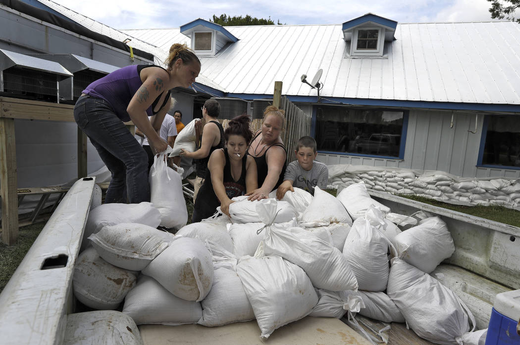 Krystal Day, of Homosassa, Fla., left, leads a sandbag assembly line at the Old Port Cove restaurant Tuesday, Oct. 9, 2018, in Ozello, Fla. Employees were hoping to protect the restaurant from flo ...