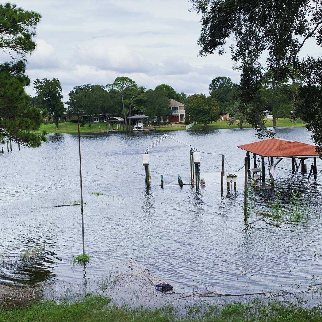 This photo provided by April Sarver shows a flooded neighborhood boat dock in Fort Walton Beach, Fla., Tuesday, Oct. 9, 2018. A fast and furious Hurricane Michael sped toward the Florida Panhandle ...