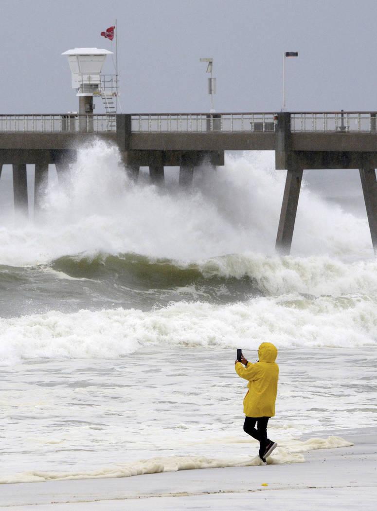 A beachgoer take photos of the waves on Wednesday Oct. 10, 2018, on Okaloosa Island in Fort Walton Beach, Fla., behind the boardwalk as Hurricane Michael impacts the coast. (Nick Tomecek/Northwest ...