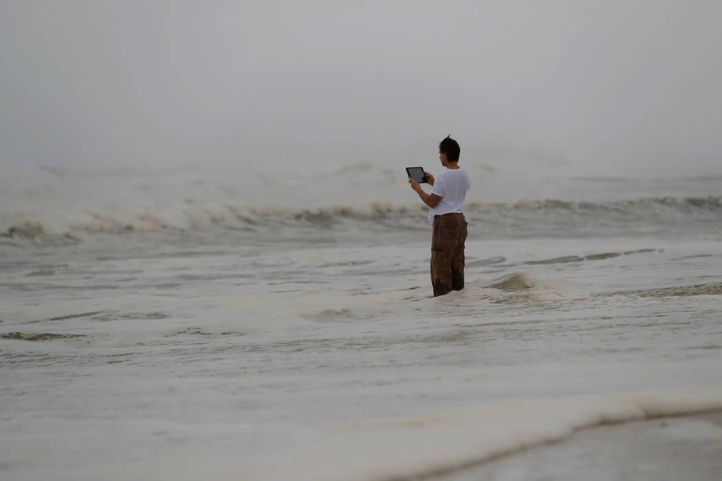Peter Malave records the surf from encroaching Hurricane Michael, which is expected to make landfall today, in Panama City Beach, Fla., Wednesday, Oct. 10, 2018. The hurricane center says Michael ...
