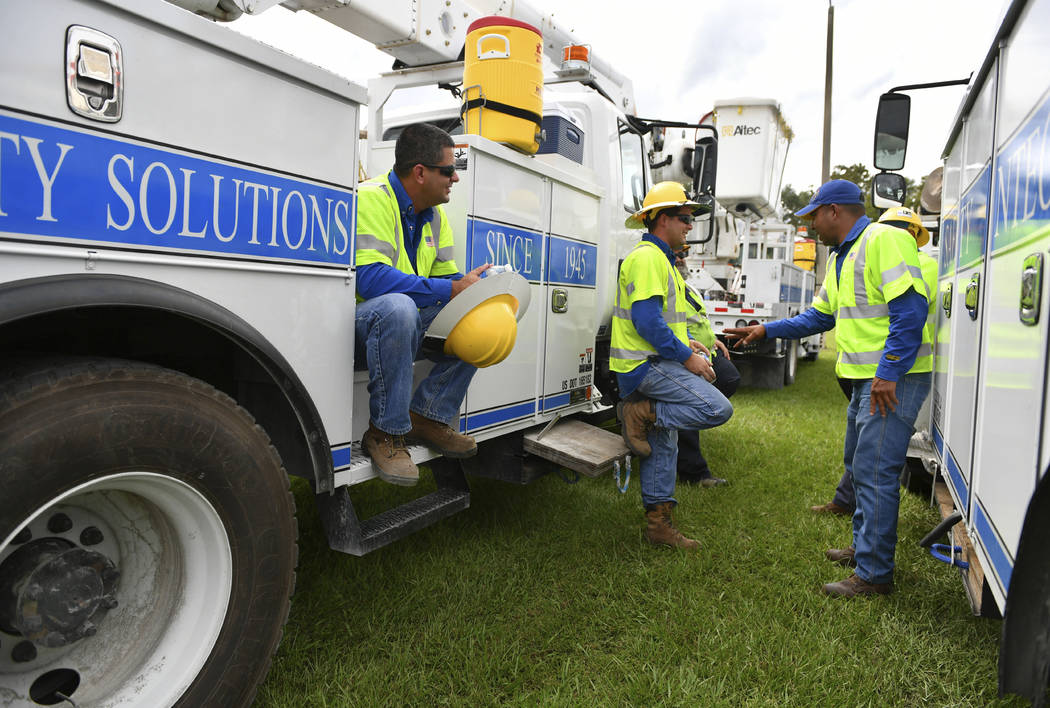 Pike Electric power restoration workers wait instructions after arriving at the Saraosta Fairgrounds on Tuesday, Oct. 9, 2018. Florida Power & Light is staging contractors in Sarasota, Fla, in ...