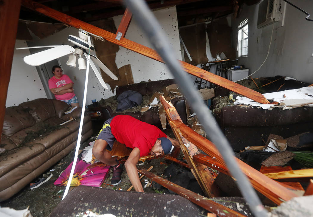 Dorian Carter looks under furniture for a missing cat after several trees fell on their home during Hurricane Michael in Panama City, Fla., Wednesday, Oct. 10, 2018. Supercharged by abnormally war ...