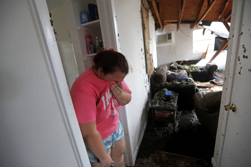 Kaylee O'Brian weeps inside her home after several trees fell on it during Hurricane Michael in Panama City, Fla., Wednesday, Oct. 10, 2018. (AP Photo/Gerald Herbert)