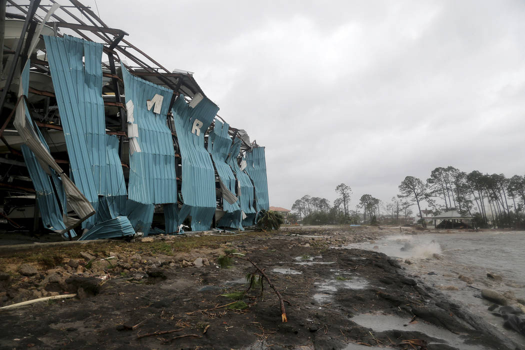 A marina warehouse is damaged at the Port St. Joe Marina, Wednesday, Oct. 10, 2018 in Port St. Joe, Fla. Supercharged by abnormally warm waters in the Gulf of Mexico, Hurricane Michael slammed int ...