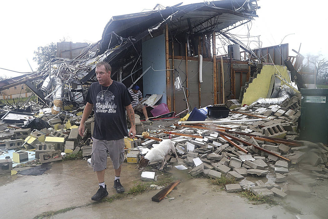 Brian Bon inspects damages in the Panama City downtown area after Hurricane Michael made landfall in Panama City, Fla., Wednesday, Oct. 10, 2018. Supercharged by abnormally warm waters in the Gulf ...