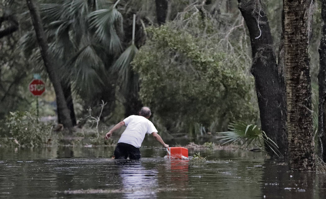 A resident of St. Marks, Fla., rescues a cooler out of the floodwaters near his home Wednesday, Oct. 10, 2018. Powerful Hurricane Michael slammed into the Florida Panhandle with terrifying winds o ...
