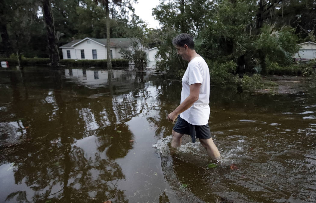 John Gouge walks through flood waters as he goes to check on the post office Wednesday, Oct. 10, 2018, in St. Marks, Fla. Supercharged by abnormally warm waters in the Gulf of Mexico, Hurricane Mi ...