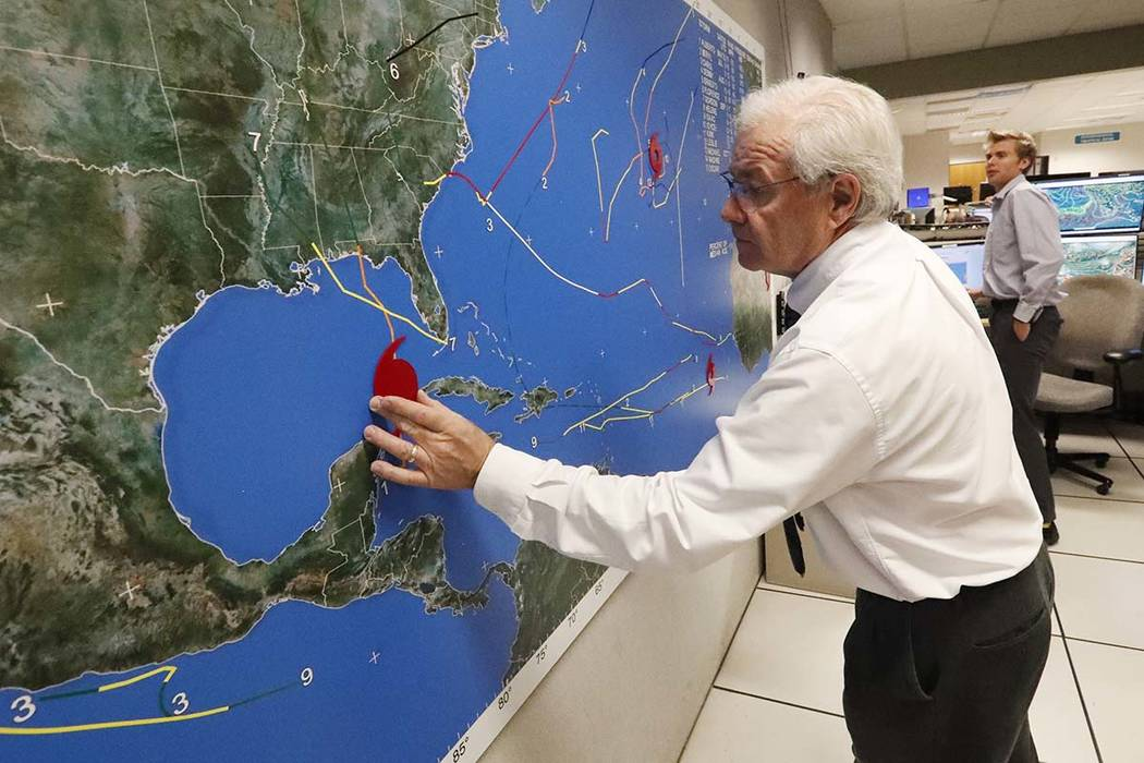National Oceanic and Atmospheric Administration public affairs officer Dennis Feltgen updates the progress of Hurricane Michael on a large map, Tuesday, Oct. 9, 2018, at the Hurricane Center in Mi ...