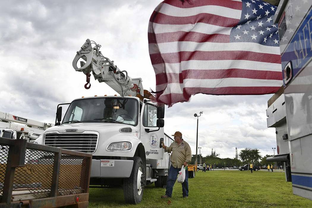 An employee of Southern Electric Corporation from Flowood, Miss., climbs out of the cab of his truck after arriving at the Sarasota Fairgrounds Tuesday, Oct. 9, 2018. Florida Power & Light is ...