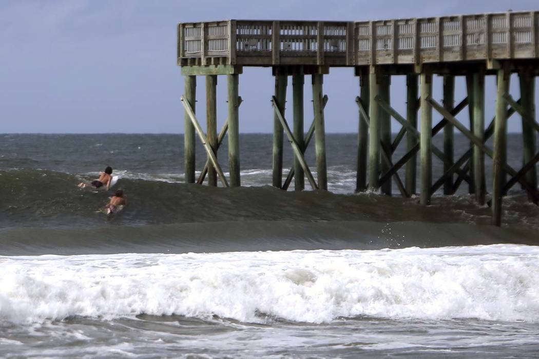 Surfers paddle past the St. Andrews State Park Pier Tuesday, Oct.9, 2018, at Panama City Beach, Fla. (Patti Blake/News Herald via AP)
