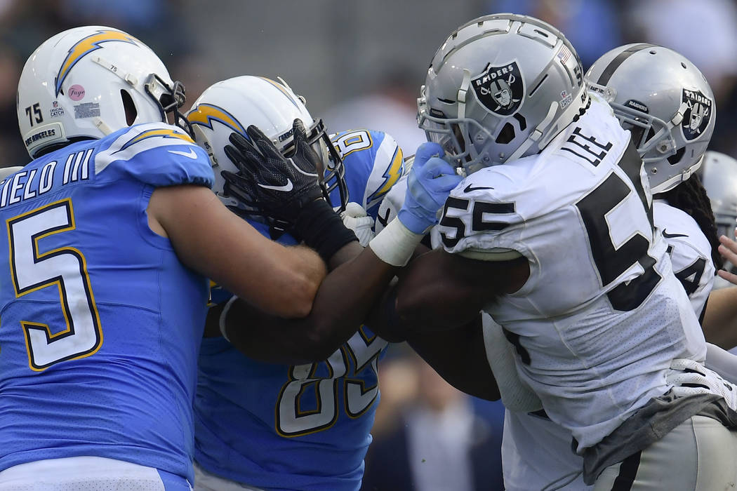 Los Angeles Chargers tight end Antonio Gates, left, and Oakland Raiders linebacker Marquel Lee (55) scuffle after a play during the second half of an NFL football game Sunday, Oct. 7, 2018, in Car ...