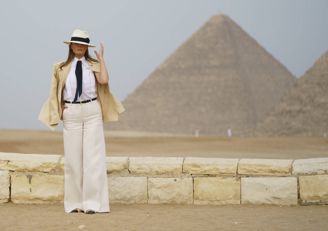 First lady Melania Trump reaches for her hat as she pauses for media during a visit to the historical Giza Pyramids site near Cairo, Egypt on Saturday, Oct. 6, 2018. Trump is visiting Africa on he ...