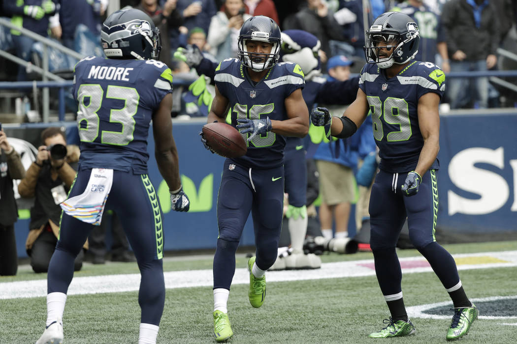 "Seattle Seahawks wide receiver Tyler Lockett, center, does a ""jump rope"" celebration with wide receiver David Moore, left, and wide receiver Doug Baldwin, right, after making a catch for ..."