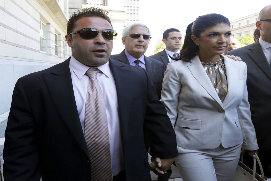 "In this July 30, 2013 file photo, ""The Real Housewives of New Jersey"" stars Giuseppe ""Joe"" Giudice, left, and his wife, Teresa Giudice, walk out of Martin Luther King Jr. (AP Photo/Julio Cortez, File)"