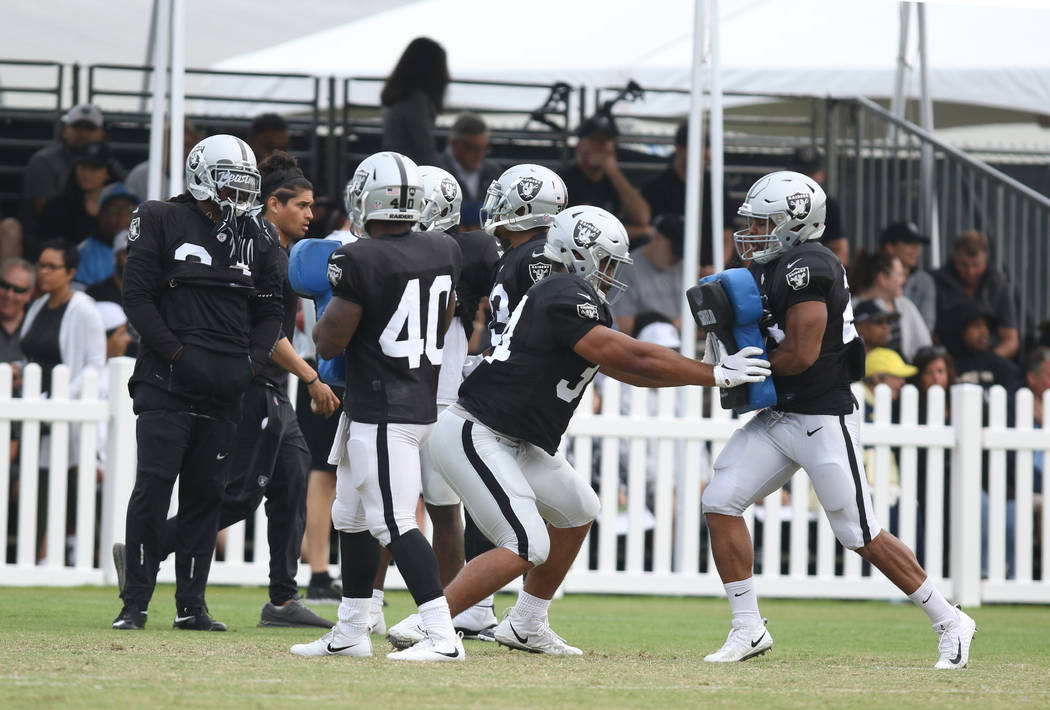 Oakland Raiders running backs Chris Warren (34) hits a pad held by Doug Martin (28) at the team's NFL training camp in Napa, Calif., Wednesday, Aug. 8, 2018. Heidi Fang Las Vegas Review-Journal @H ...