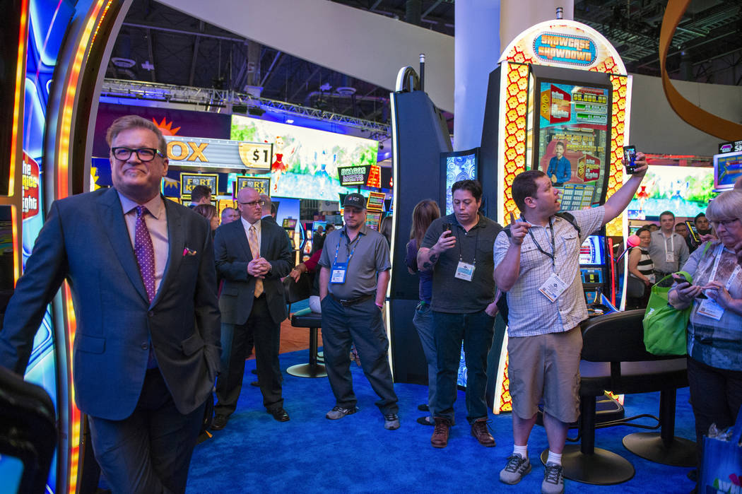Famed gameshow host Drew Carey stands next to one of the IGT Price is Right slot games as a fan takes a selfie with the entertainment icon at the 18th annual Global Gaming Expo at Sands Expo and C ...