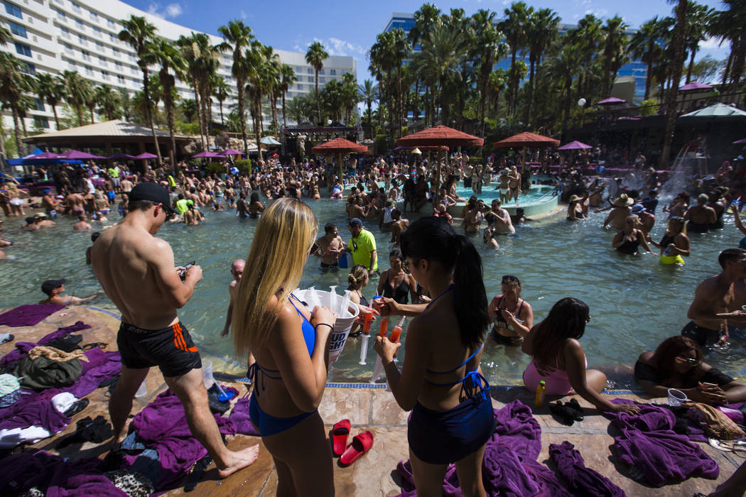 Shot runners Ashley Sells, left, and Ann Gonzalez offer vodka cranberry pineapple shots in syringes at the Rehab dayclub at Hard Rock Hotel in Las Vegas on Saturday, June 24, 2017. Chase Stevens L ...