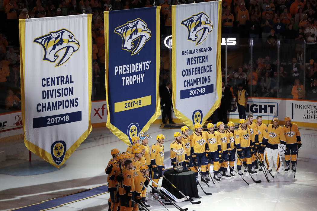 Nashville Predators players stand with the Presidents' Trophy as the banners for the Presidents' Trophy, Central Division Champions and Western Conference Champions are raised before an NHL hockey ...