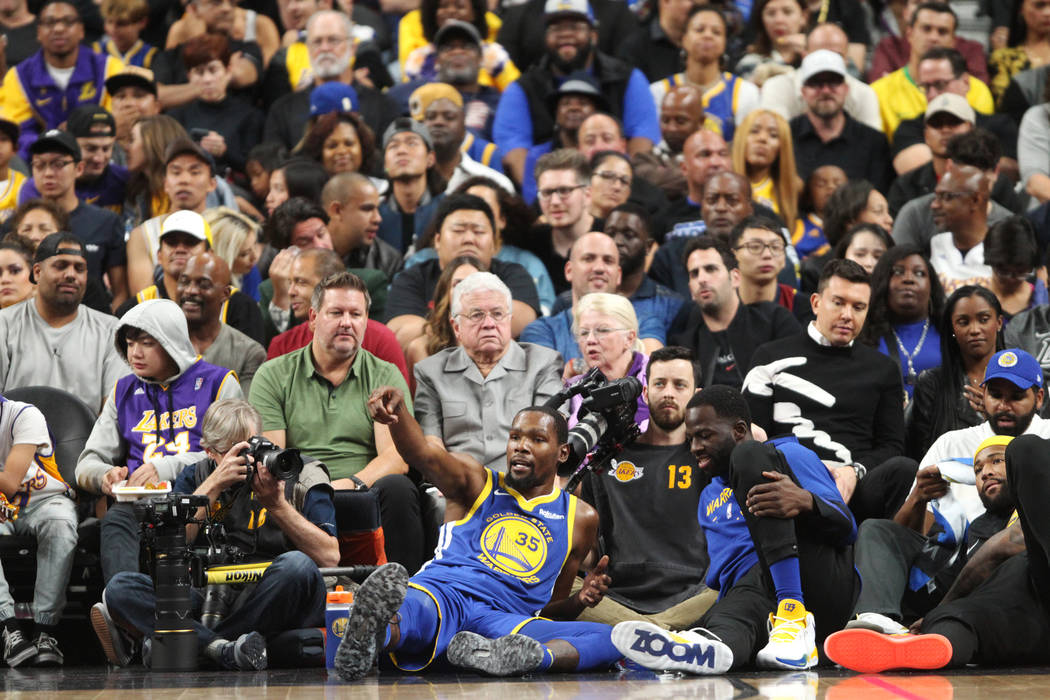 Golden State Warriors forward Kevin Durant (35), center, sits on the floor after getting fouled out during an NBA preseason game against the Golden State Warriors at T-Mobile Arena in Las Vegas, W ...