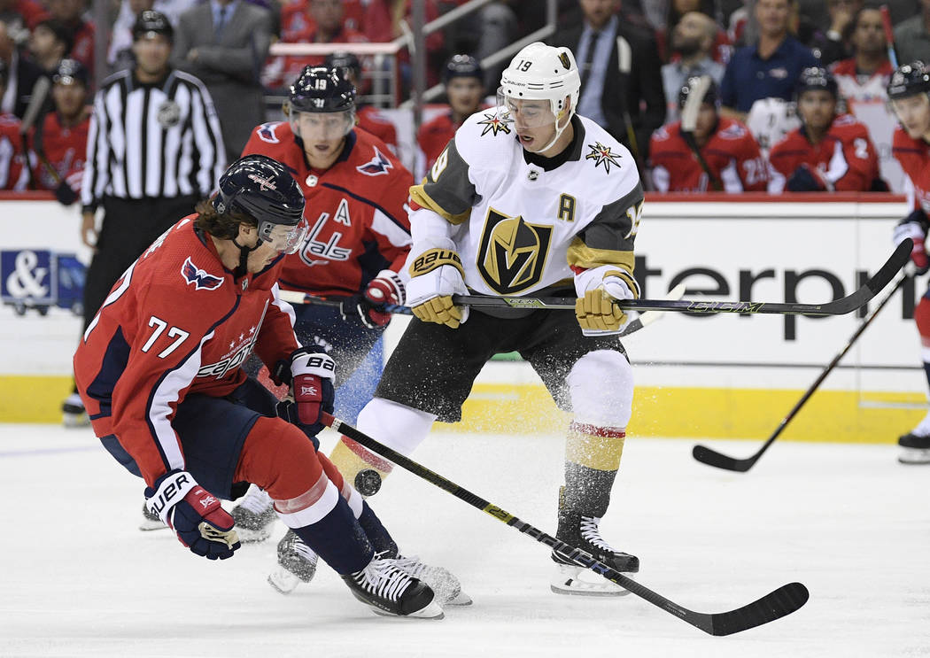 Vegas Golden Knights right wing Reilly Smith (19) battles for the puck against Washington Capitals right wing T.J. Oshie (77) during the first period of an NHL hockey game Wednesday, Oct. 10, 2018 ...
