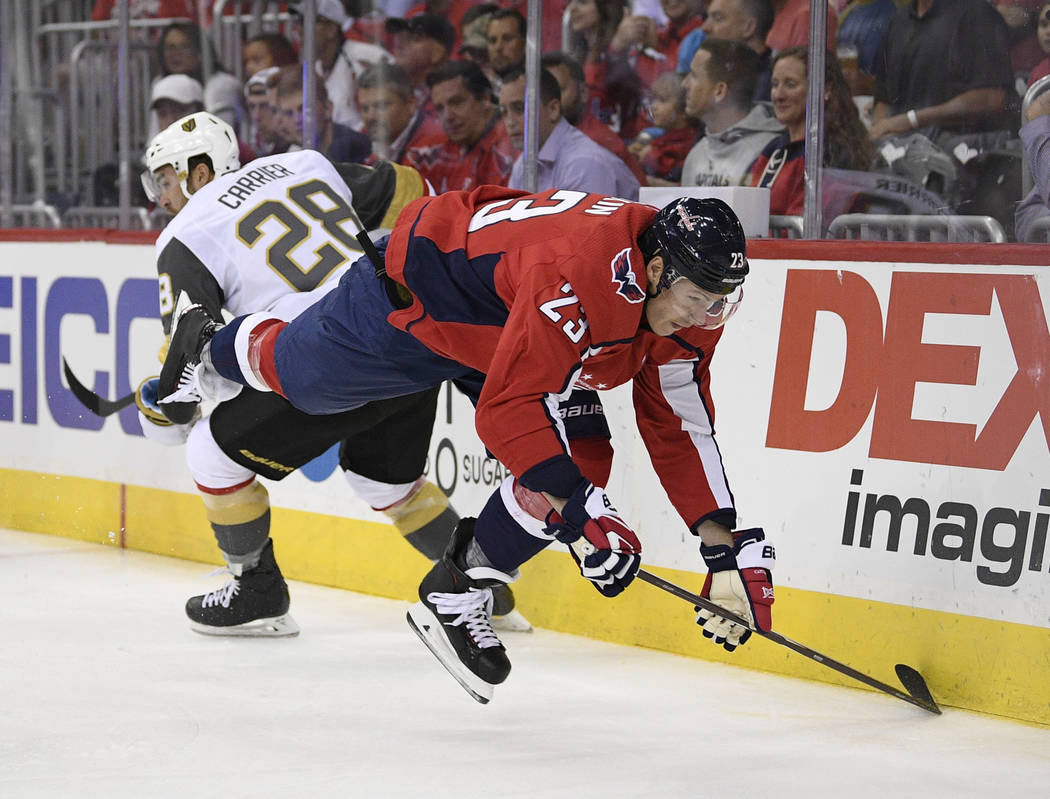 Washington Capitals right wing Dmitrij Jaskin (23) falls to the ice next to Vegas Golden Knights left wing William Carrier (28) during the first period of an NHL hockey game Wednesday, Oct. 10, 20 ...