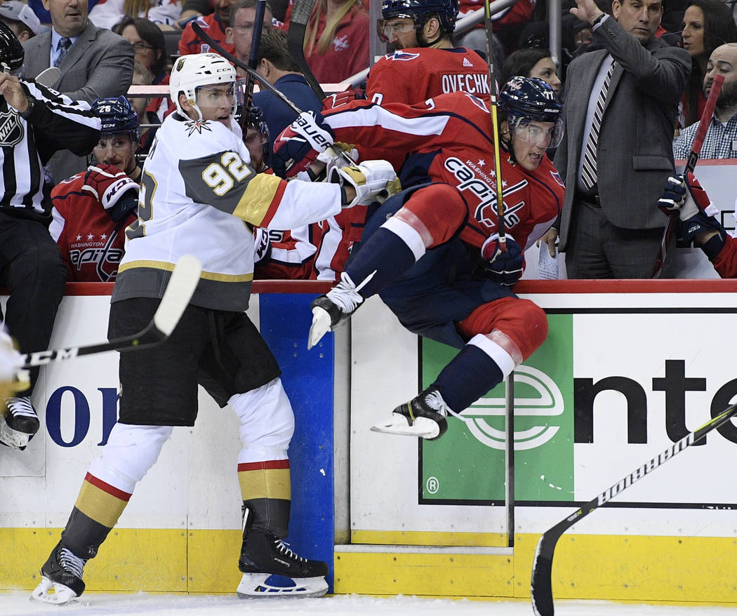 Vegas Golden Knights left wing Tomas Nosek (92) checks Washington Capitals right wing T.J. Oshie (77) during the second period of an NHL hockey game Wednesday, Oct. 10, 2018, in Washington. (AP Ph ...