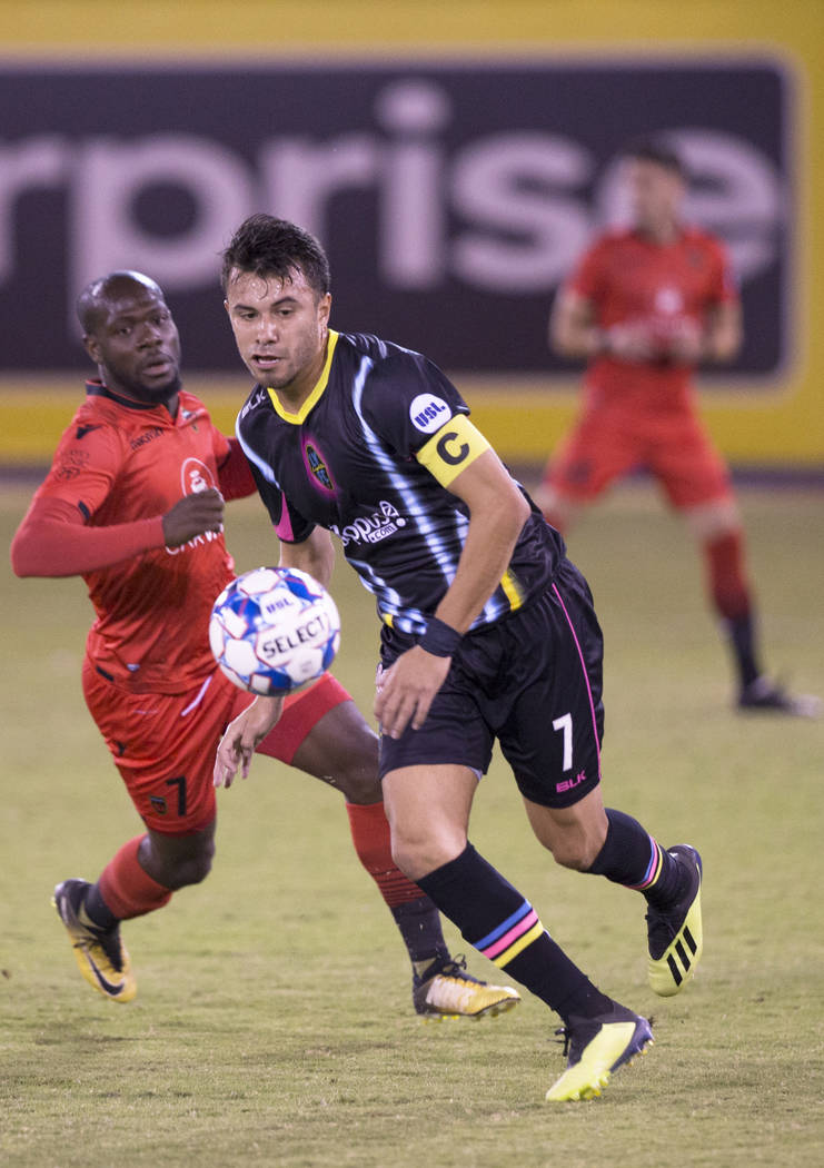 Las Vegas Lights FC midfielder Carlos Alvarez (7) pushes the ball up field past Phoenix Rising forward Billy Forbes (7) in the first half on Wednesday, Oct. 10, 2018, at Cashman Field, in Las Vega ...