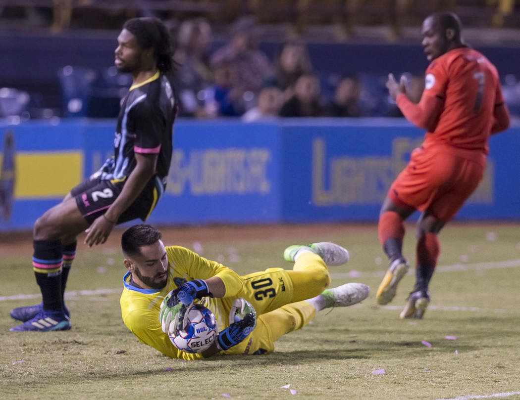 Las Vegas FC goalkeeper Thomas Olsen (30) makes a save against Phoenix Rising forward Billy Forbes (7) with the help of defender Joel Huiqui (3) in the first half during their United Soccer League ...