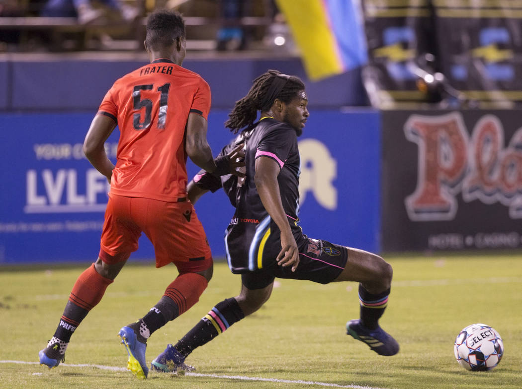 Las Vegas Lights defender Carter Manley (2) pushes the ball up field past Phoenix Rising forward Kevaughn Frater (51) in the first half on Wednesday, Oct. 10, 2018, at Cashman Field, in Las Vegas. ...
