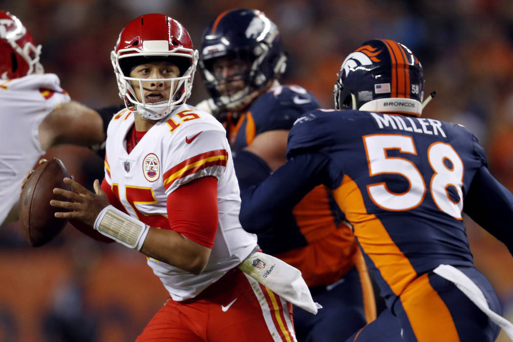 Kansas City Chiefs quarterback Patrick Mahomes (15) scrambles as Denver Broncos linebacker Von Miller (58) pursues during the first half of an NFL football game in Denver on Oct. 1, 2018. The Chie ...