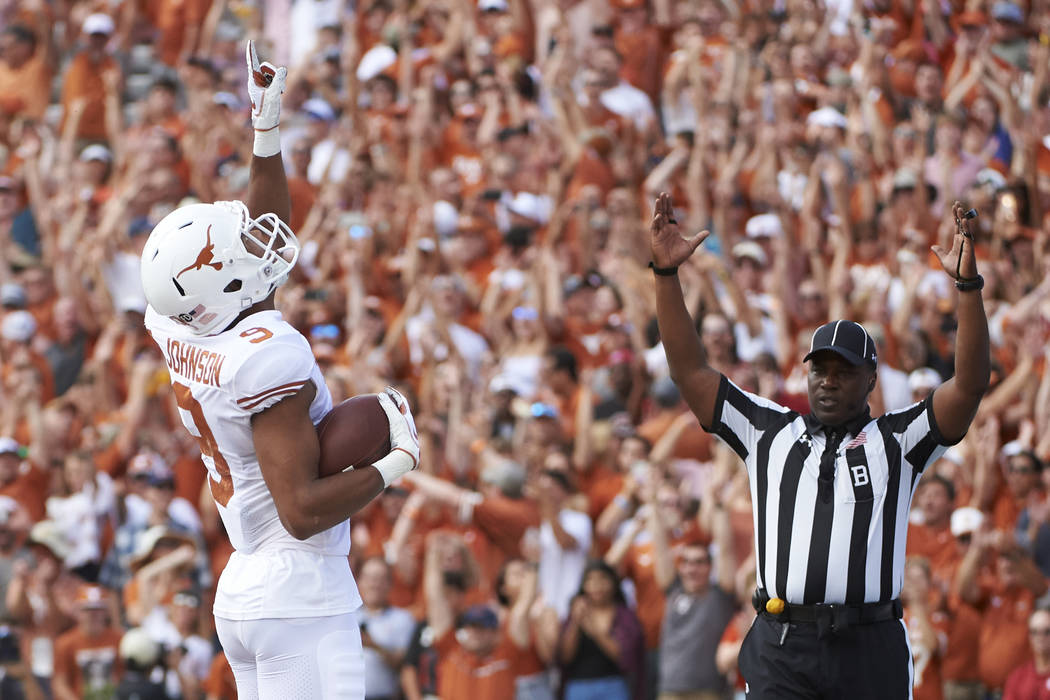 In this Saturday, Oct. 6, 2018, file photo, Texas wide receiver Collin Johnson (9) celebrates after scoring a touchdown on a 2-yard reception during the first half of an NCAA college football game ...