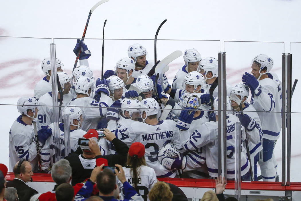 Toronto Maple Leafs defenseman Morgan Rielly (44) celebrates with teammates after scoring in overtime of an NHL hockey game against the Chicago Blackhawks Sunday, Oct. 7, 2018, in Chicago. (AP Pho ...