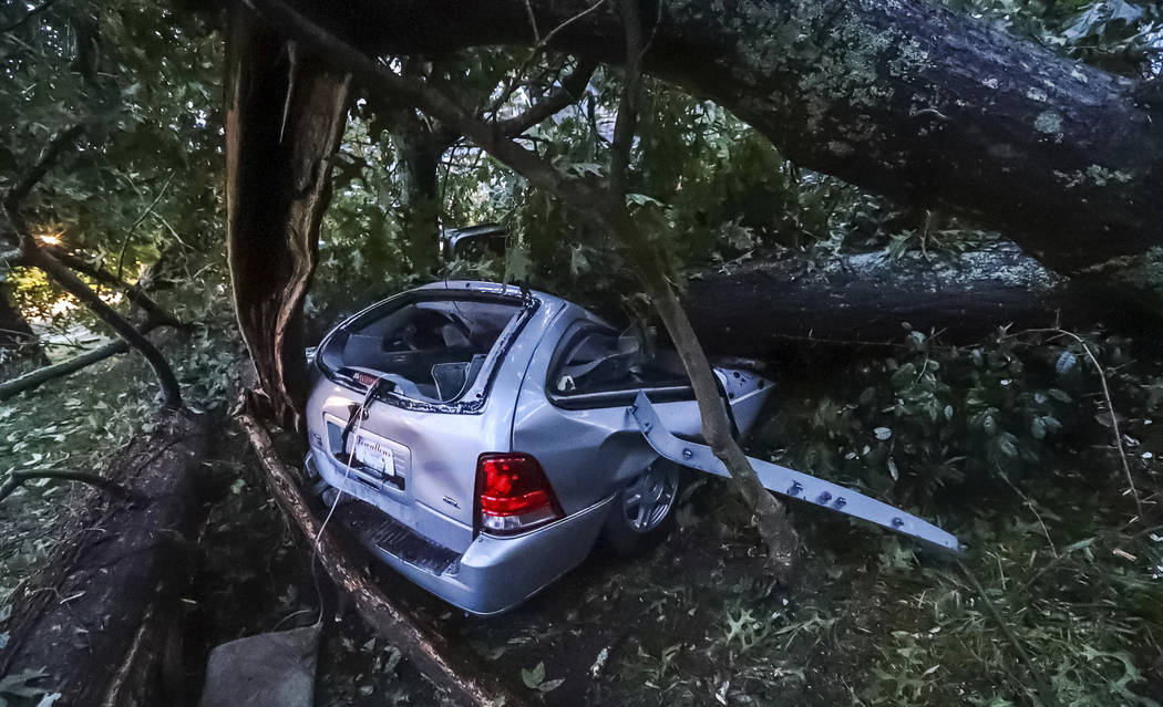 A vehicle sits under a fallen tree where an occupant was trapped due to tropical storm winds brought by Hurricane Michael, Thursday, Oct. 11, 2018, in Atlanta. Firefighters rescued the woman and s ...
