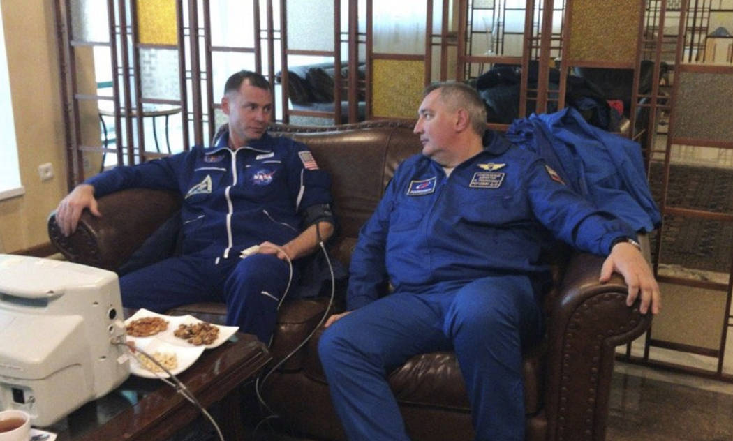 NASA Astronaut Nick Hague, left, and Roscosmos Director Dmitry Rogozin sit in Dzhezkazgan, Kazakhstan on Thursday, Oct. 11, 2018, after an emergency landing following the failure of a Russian boos ...