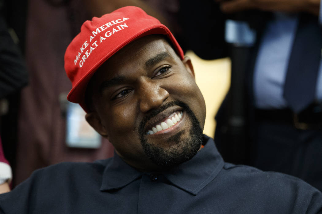 Rapper Kanye West smiles as he listens to a question from a reporter during a meeting in the Oval Office of the White House with President Donald Trump, Thursday, Oct. 11, 2018, in Washington. (Ev ...