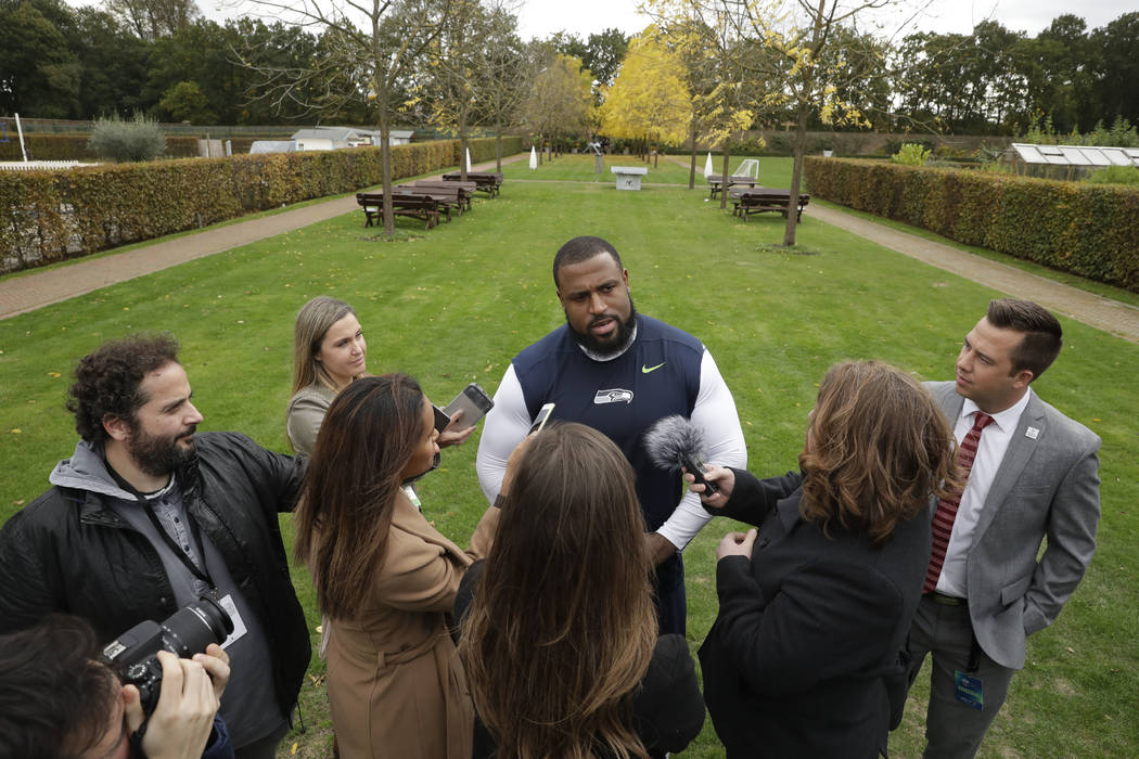 Seattle Seahawks' offensive tackle Duane Brown speaks in a media huddle after an NFL training session at the Grove Hotel in Chandler's Cross, Watford, England, Friday, Oct. 12, 2018. The Seattle S ...