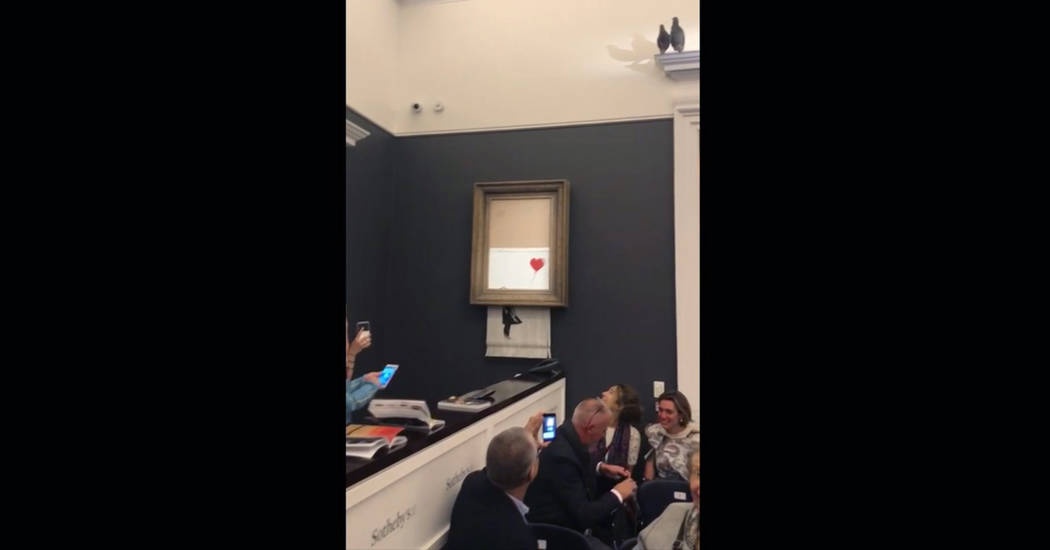 """In this grab taken from video on Friday, Oct. 5, 2018 people watch as the spray-painted canvas """"Girl with Balloon"""" by artist Banksy is shredded at Sotheby's, in London, A Banksy artwork ..."""