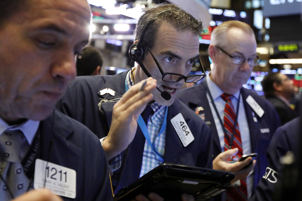 Gregory Rowe, center, works with fellow traders on the floor of the New York Stock Exchange, Thursday, Oct. 11, 2018. The market's recent decline was set off by a sharp drop in bond prices and a c ...