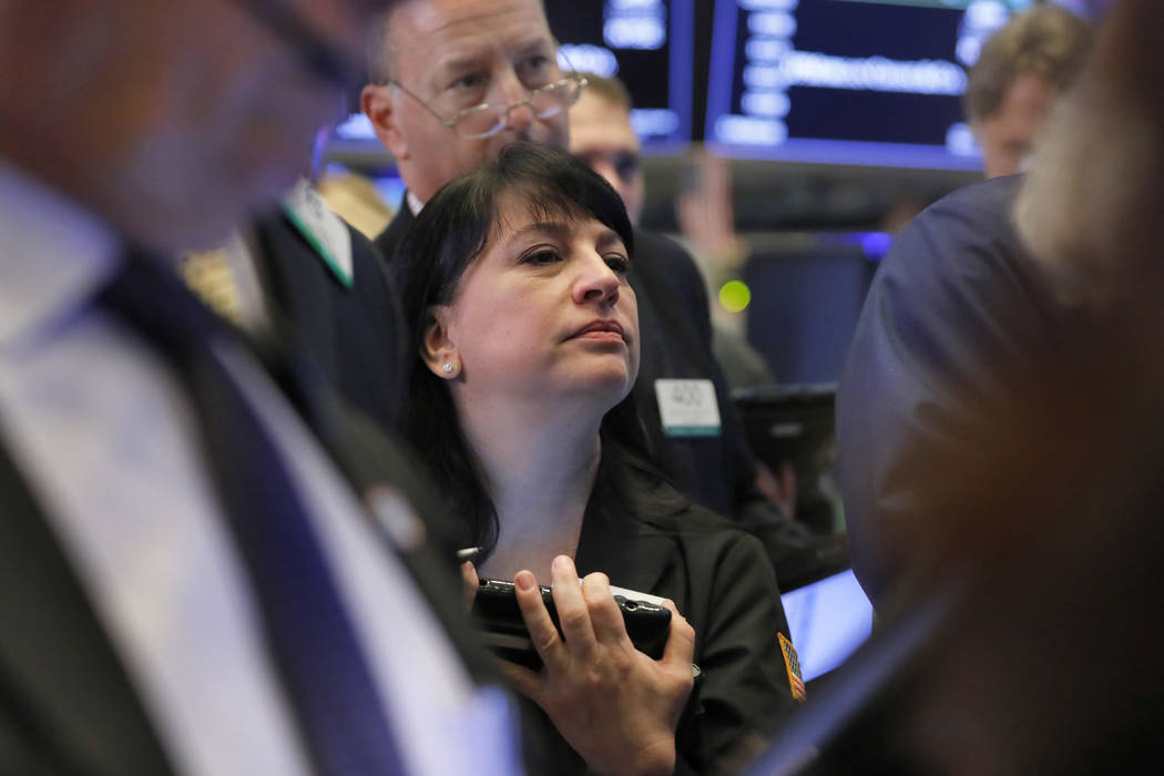 Trader Phyllis Arena Woods works on the floor of the New York Stock Exchange, Thursday, Oct. 11, 2018. U.S. stocks are mostly lower in unsteady trading one day after their biggest drop since Febru ...
