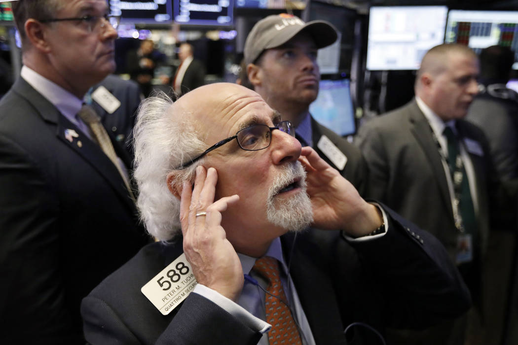 Trader Peter Tuchman works on the floor of the New York Stock Exchange, Thursday, Oct. 11, 2018. The market's recent decline was set off by a sharp drop in bond prices and a corresponding increase ...