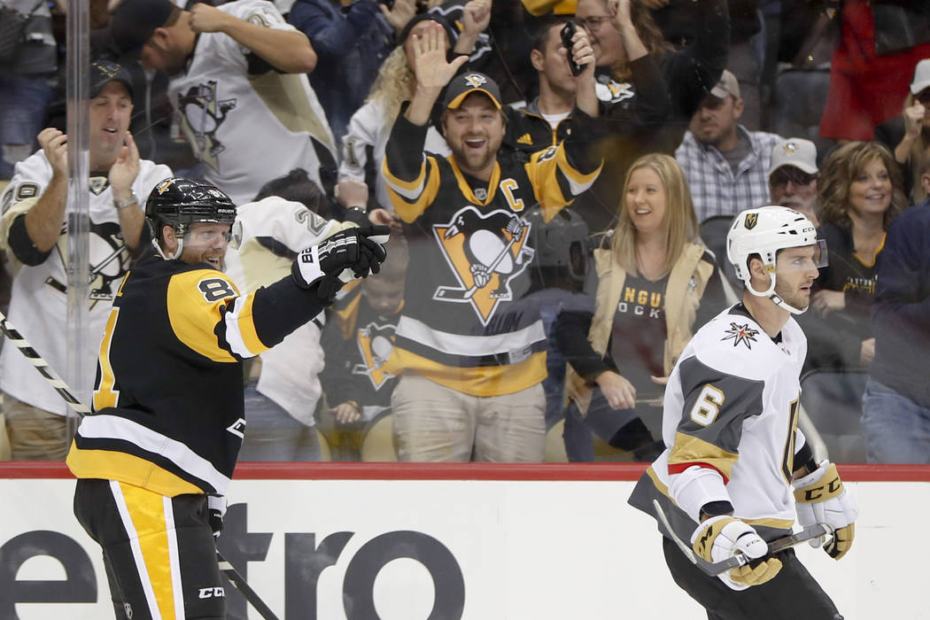 Pittsburgh Penguins' Phil Kessel, left, celebrates behind Vegas Golden Knights' Colin Miller after scoring his first goal during the second period, and second goal of an NHL hockey game, Thursday, ...