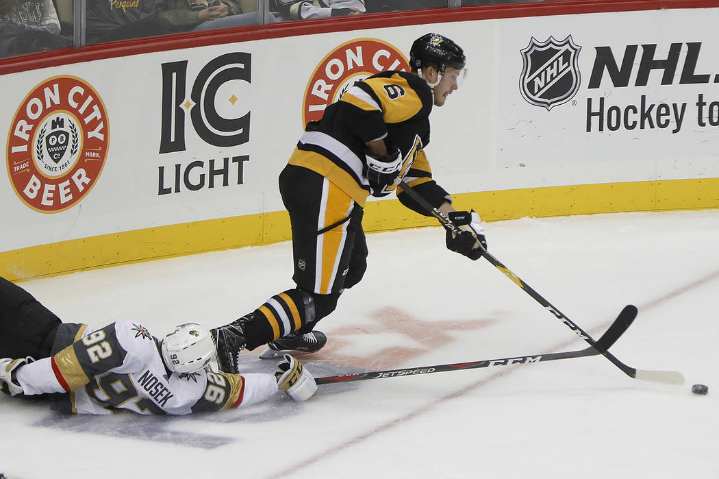 Vegas Golden Knights' Tomas Nosek (92) tries for the puck from his back as Pittsburgh Penguins' Jamie Oleksiak (6) skates with it during the first period of an NHL hockey game Thursday, Oct. 11, 2 ...