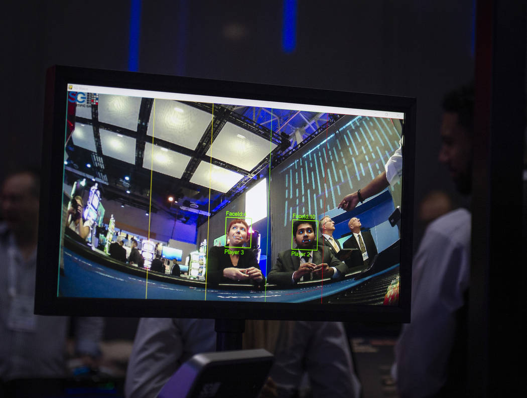 Attendees play poker that uses computer vision that offers real-time ratings and table game analytics at the Scientific Games booth at the 18th annual Global Gaming Expo at Sands Expo and Conventi ...
