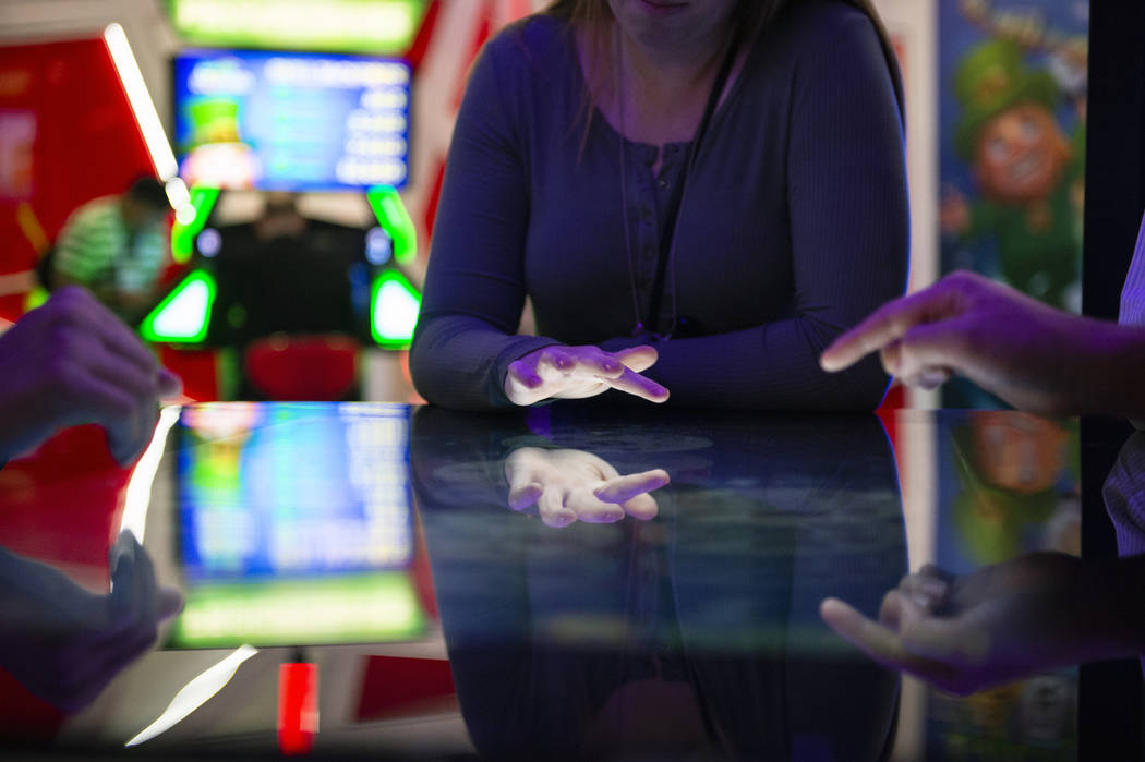 Attendees play a Deal or No Deal themed table game that uses touch screen technology at the Gamblit booth at the 18th annual Global Gaming Expo at Sands Expo and Convention Center in Las Vegas, Th ...