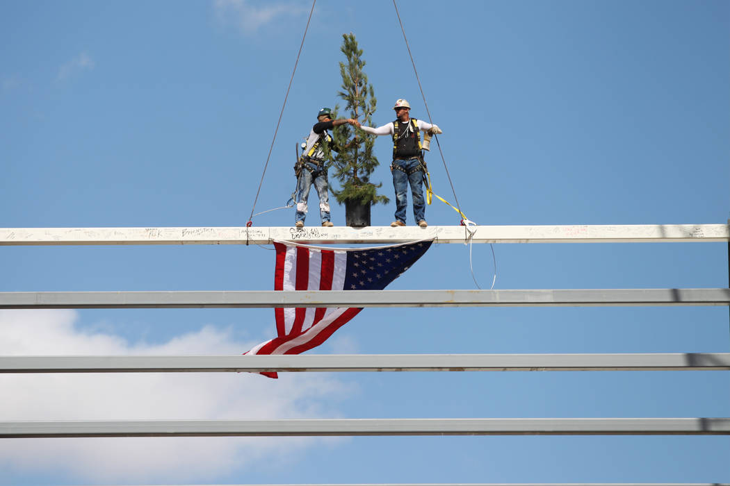 Workers shake hands after installing a steel beam into place during a topping off ceremony at the Las Vegas Ballpark construction site in Las Vegas, Thursday, Oct. 11, 2018. Erik Verduzco Las Vega ...