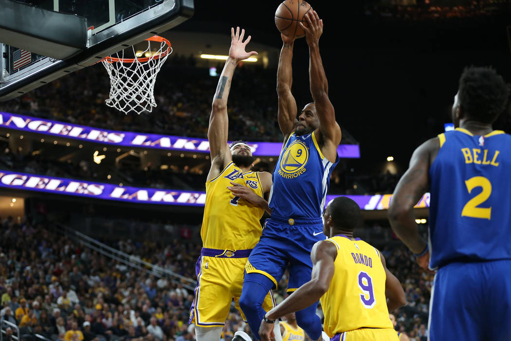 Golden State Warriors guard Andre Iguodala (9) goes up for a shot under pressure from Los Angeles Lakers center JaVale McGee (7) in the NBA game at T-Mobile Arena in Las Vegas, Wednesday, Oct. 10, ...
