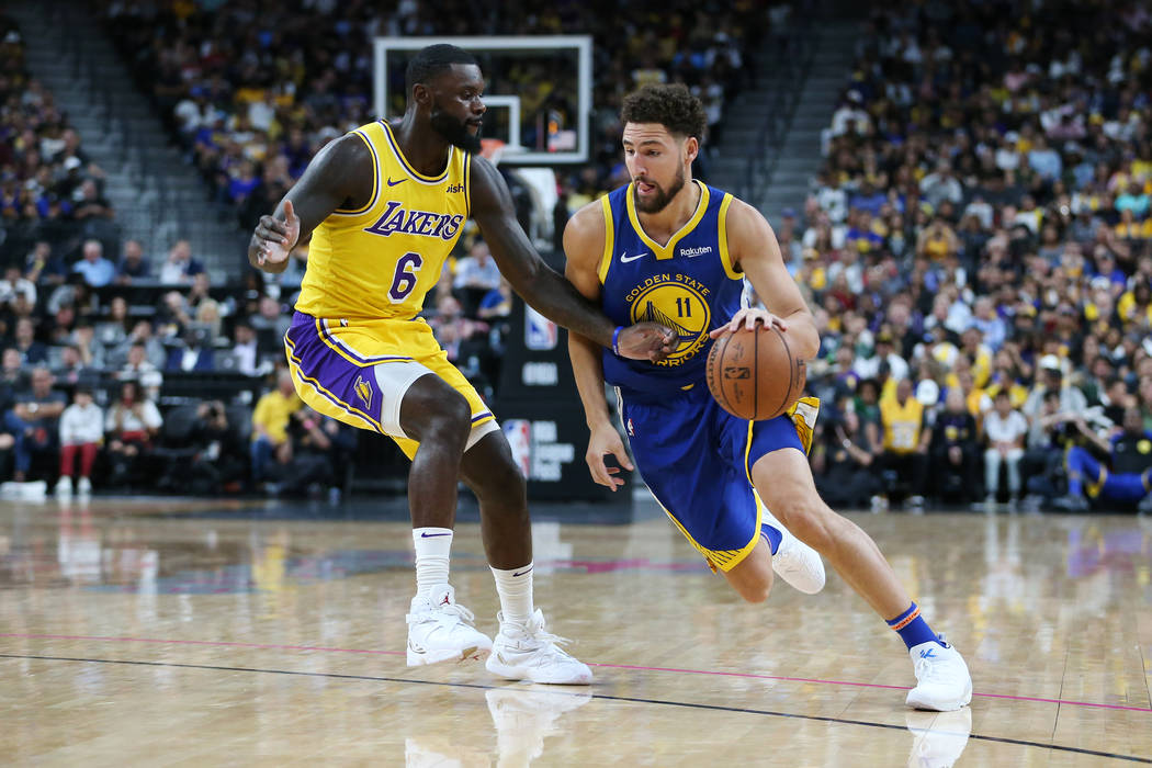 Golden State Warriors guard Klay Thompson (11) drives the ball to the hoop against Los Angeles Lakers guard Lance Stephenson (6) in the NBA game at T-Mobile Arena in Las Vegas, Wednesday, Oct. 10, ...