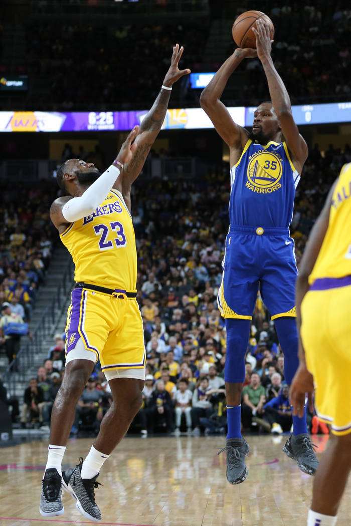 Golden State Warriors forward Kevin Durant (35) takes a shot under pressure from Los Angeles Lakers forward LeBron James (23) in the NBA preseason game at T-Mobile Arena in Las Vegas, Wednesday, O ...